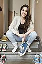 Smiling young woman sitting on staircase holding sneakers - PESF000307
