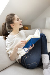 Happy woman sitting on couch reading book - PESF000319