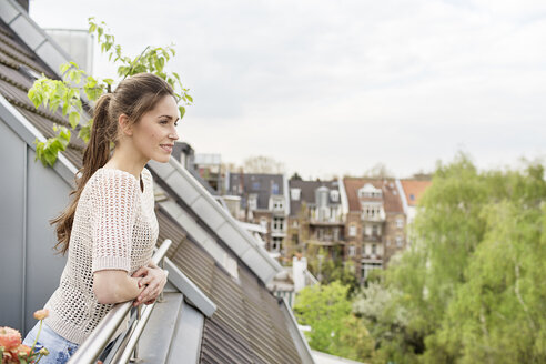 Smiling young woman standing on balcony - PESF000322