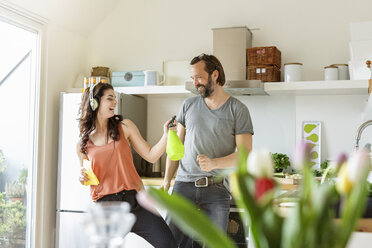 Happy woman with man in kitchen cleaning and listening to music - PESF000328