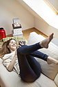Happy woman lying on couch using mobile device - PESF000334