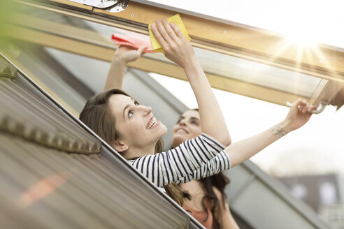 Smiling young woman cleaning roof window - PESF000337