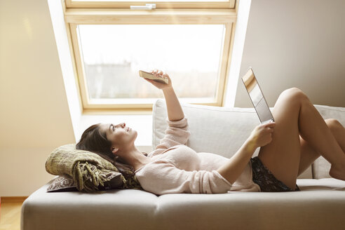 Relaxed woman lying on couch with cell phone and laptop - PESF000340