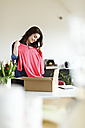 Smiling woman at home unpacking parcel with garment - PESF000343
