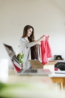 Smiling woman at home unpacking parcel with garment - PESF000346