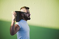 Man with skateboard on his shoulders - RAEF001365