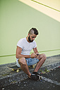 Man sitting on his skateboard at carb text messaging - RAEF001368