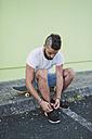Skateboarder tying his shoe - RAEF001371