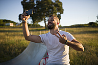 Man taking selfie while showing victory sign - RAEF001383
