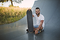 Smiling skateboarder sitting on ramp in a skatepark - RAEF001386