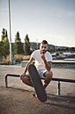 Portrait of skateboarder sitting in a skatepark - RAEF001389