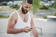 Young man with shaved head looking at cell phone - RAEF001395