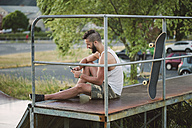 Smiling skateboarder using his smartphone in a skatepark - RAEF001398