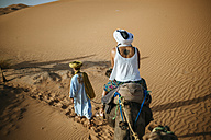 Woman riding a camel in the desert with Berber guide - KIJF000699