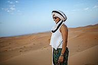 Woman standing in the desert, wearing turban - KIJF000708