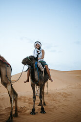 Woman with turban riding a camel in the desert - KIJF000717