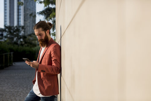 Fashionable young man leaning against wall looking at smartphone - MAUF000726