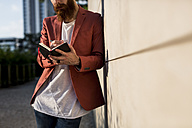 Fashionable young man with full  beard leaning against wall writing at his notebook - MAUF000729
