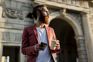 Young man with coffee and smartphone looking at distance - MAUF000738