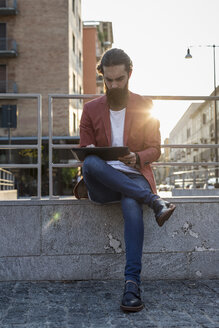 Young man sitting on a wall in the city using tablet - MAUF000741