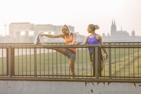 Two young women stretching on bridge - MADF001087