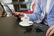 Close-up of businessman using cell phone in a cafe - MAUF000747