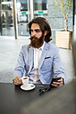 Stylish businessman holding cell phone in a cafe - MAUF000750