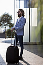 Stylish businessman walking with suitcase outdoors - MAUF000753