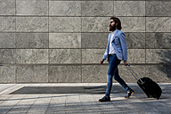 Stylish businessman walking with suitcase outdoors - MAUF000756