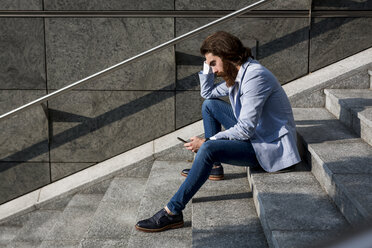 Stylish businessman using cell phone on stairs outdoors - MAUF000762