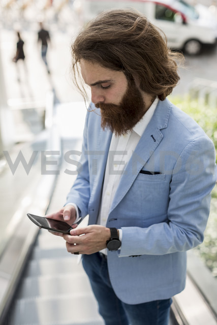 Stylish businessman using cell phone on escalator - MAUF000768 - Mauro Grigollo/Westend61