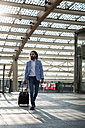 Stylish businessman walking with suitcase - MAUF000771