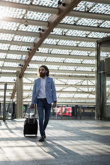 Stylish businessman walking with suitcase - MAUF000771