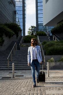 Stylish businessman walking with suitcase outdoors - MAUF000777