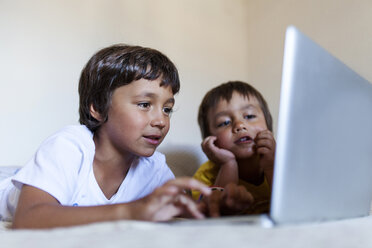 Two little boys lying on bed looking at laptop - VABF000735