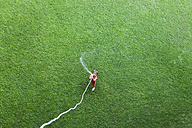Little boy standing on lawn playing with garden hose, top view - VABF000738