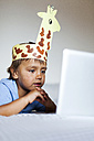 Little boywith self-made headdress lying on bed looking at laptop - VABF000744
