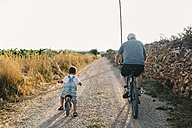 Back view of little boy and his great-grandfather on bicycle tour - JRFF000809