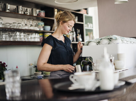 Woman in a cafe preparing milk froth for coffee - KNSF000198