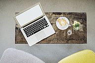 Laptop and cup of coffee on table in a cafe - KNSF000219