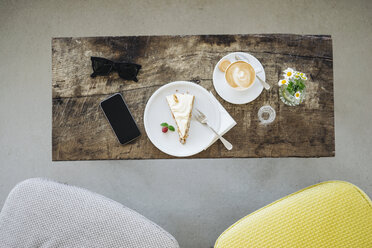 Cell phone, sunglasses, cake and cup of coffee on table in a cafe - KNSF000225