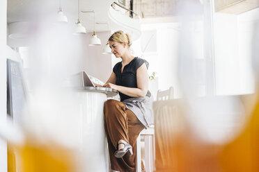 Woman using digital tablet in a cafe - KNSF000228