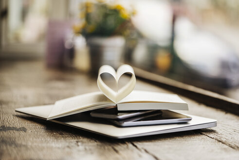 Book with heart-shaped pages on stack of mobile devices - KNSF000243
