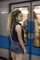 Woman waiting on underground station platform - MAUF000796