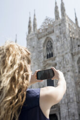Italy, Milan, back view of tourist taking picture of cathedral with cell phone - MAUF000799