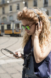 Young woman with headphones and mirrored sunglasses looking at her smartphone - MAUF000802