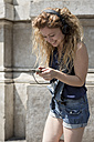 Smiling young woman with headphones text messaging - MAUF000805