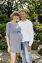 Happy couple with pregnant woman standing in garden - MFF003010