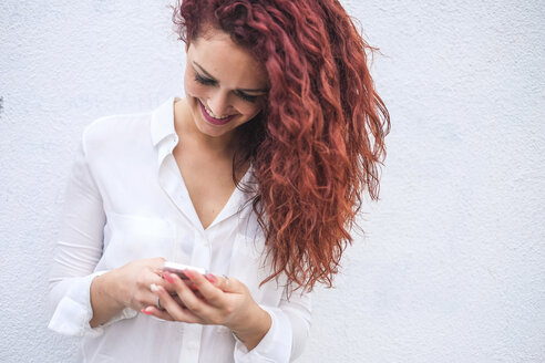 Redheaded young woman looking at cell phone - SIPF000777