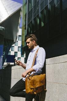 Ireland, Dublin, businessman with shoulder bag leaning against wall using cell phone - BOYF000507